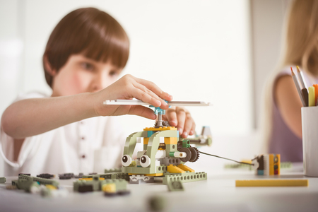 Orderly kid making toy from constructor during lesson. Toys of future concept Stock Photo