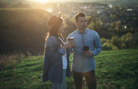 Couple standing in nature in summer sunset with plastic cups. Happy woman is looking at thoughtful boyfriend. They are holding hands