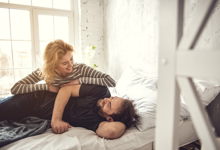 Smiling attractive lady is leaning over her partner while he is lying on cot. They are catching each-other sight with tenderness. Happy leisure with lover concept