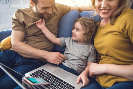 Happy spouse with their kid exploiting smartphone and laptop in sitting-room. They are sitting beside while dad and little boy are tenderly touching each-other. Family having fun together concept Stockfoto