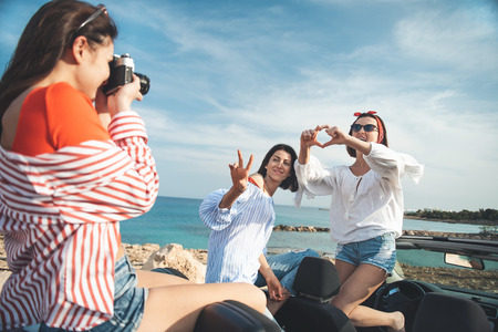 Best memories. Pleasant cute young woman is holding camera and taking photos of her female friends against blue ocean while sitting on cabriolet. They are expressing happiness while posing with joy