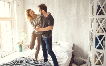 Happy two young people are standing on bed and hugging each other. They are looking into partner eyes with love. Man is holding woman hand and supporting her while she is staying in graceful pose Stock Photo