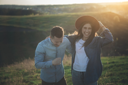 Sincere smile. Waist up of cheerful man and woman standing close to each other in green nature surrounded by hills. They are laughing enthusiastically among beautiful evening nature