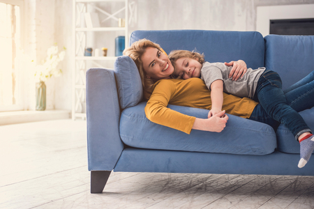 Grinning mom is relaxing on comfortable sofa while son is lying on parent. She is tenderly touching kid hand and looking at camera while he is happily having eyes-closed. Motherhood care concept Stock Photo