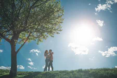 Full length of young man and girl looking at each other with love. They are embracing enjoying summer and nature together. Copy space in left side