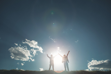 Summer of love. Full length of girl and boy rejoicing amazing sun on green meadow. They are standing close to each other with hands up facing beautiful blue sky