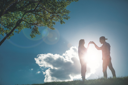 Full length of happy couple calmly looking at each other and enjoying feelings on pictorial summer landscape. They are holding hands in shape of heart