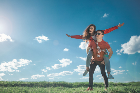 I believe we can fly. Full length of amorous couple looking at blue sky. Girl is on her boyfriend back with stretched arms. They smiling and enjoying summer weather. Copy space in left side Stock Photo