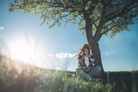 Full length of young calm woman sitting on beautiful meadow on bright sunny day. She is spending time alone reading interesting book in silence and peace. Copy space in left side