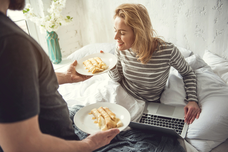 Top view of smiling woman sitting in bedroom with computer. Beloved partner is bringing her sweet pancakes and she is smelling aroma. Breakfast in bed concept
