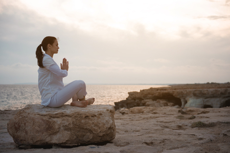 Harmony and relaxation. Full length side view profile of young woman in white clothes is sitting on big stone. She is keeping legs crossed while practicing asana with closed eyes. Copy space Stock Photo