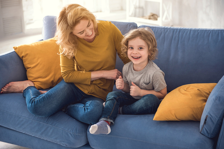 Happy family are having fun together in their comfortable house. They are sitting on sofa while mother is lovingly touching little boy. Cute child is looking at camera with joy