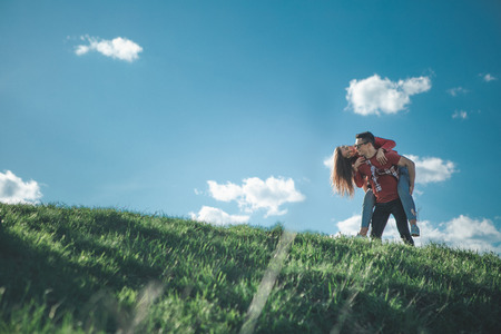 Playful look. Low angle of young nice couple among picturesque summer nature. Man carrying his woman while she looking at him with happy smile. Copy space in left side