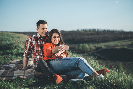 Say cheese. Full length portrait of joyful girl and boy sitting on plaid and making selfie. They are happy surrounded by pictorial landscape in summer