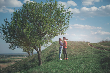Summer tenderness. Full length side view of lovely girl and man embracing on background of nature panorama. They enjoy company of each other looking in love