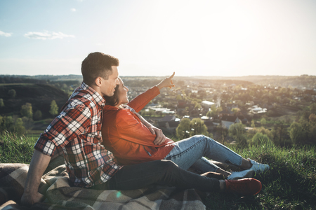 Look there. Full length side view of man and woman sitting and looking at beautiful summer sky. Delighted girl is pointing at shining sun. They are bonding to each other and smiling