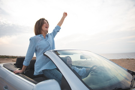 Full of happiness. Two overjoyed young attractive women are driving car while travelling along seashore. Girl is standing in cabriolet with open roof. She is feeling contentment with raised hand