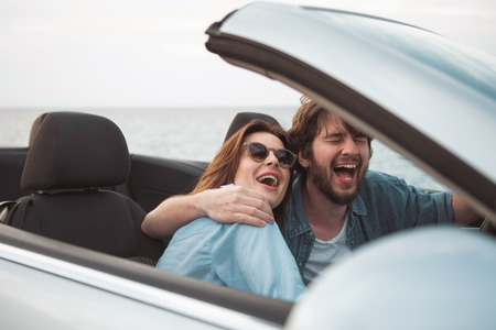 Fun together. Joyful happy couple in love is sitting in luxury cabriolet and hugging. They are driving car along seaboard and laughing. Male and female are relishing summer vacation abroad