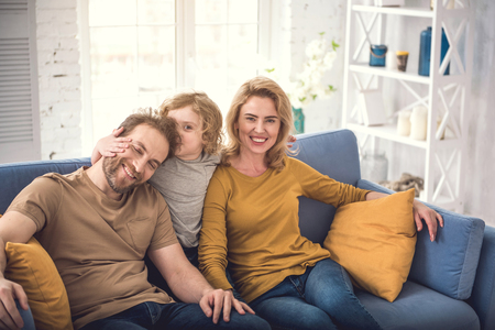 Cheerful parents are sitting with son in nice sitting-room and bonding child. Kid is kissing his doting father while man is closing eyes with bliss. Calm grinning mother is watching at camera