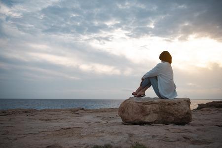 Wunderbare Aussicht. Rückansicht des nachdenklichen Mädchens am Strand in voller Länge sitzt auf einem großen runden Stein, während es den Sonnenuntergang genießt. Sie schaut auf den Ozean und denkt träumerisch. Kopieren Sie das Leerzeichen auf der linken Seite
