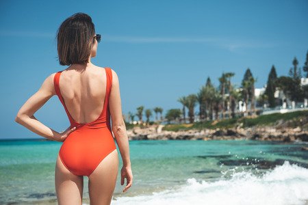 Warm day. Back of young mysterious slim girl in red swimsuit is standing on the beach and enjoying coastal view and azure ocean. Summer vacation concept. Copy space in the right side