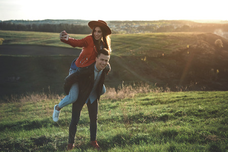 Memorize this moment. Young smiling couple enjoying summer evening in nature. Man is carrying girlfriend with cellphone on back. Copy space in right side