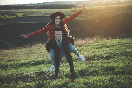 You make me fly. Full length portrait of happy girlfriend imitating flying sitting on back of boyfriend. They are full of love and delight of spending leisure together in nature Stock Photo