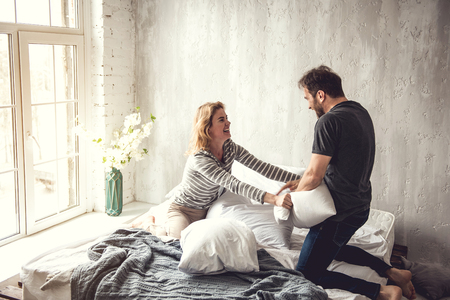 Happy couple is playing with cushions on large bed. Lady is laughing and trying to get it from man. Happy bed leisure concept