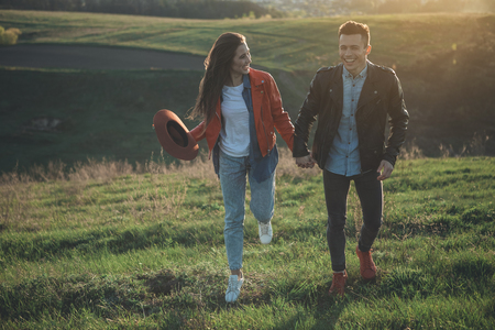 Summer joy. Cheerful couple laughing in nature. They are walking holding hands on beautiful green hill. Copy space in left side