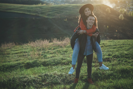 My perfect match. Full length of cheerful female embracing boy neck. They are delighted and happy walking on meadow before sunset. Copy space in left side