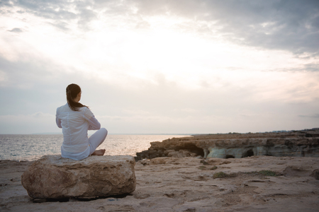 Inner harmony. Full length back view of calm girl is sitting on beach while meditating. She is practicing yoga on beach while enjoying wonderful view on the sea. Copy space in the right side