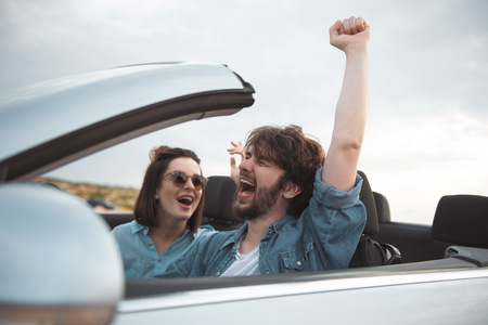 I feel free. Overjoyed young bearded man is driving car while travelling with his gorgeous girlfriend. They are enjoying weekend. Focus on screaming guy is sitting with raised hand and closed eyes Фото со стока
