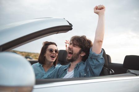 Ich fühle mich frei. Überglücklicher junger bärtiger Mann fährt Auto, während er mit seiner wunderschönen Freundin reist. Sie genießen das Wochenende. Konzentriere dich auf den schreienden Kerl, der mit erhobener Hand und geschlossenen Augen sitzt