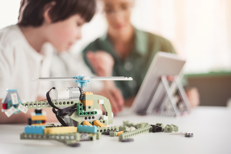 Close up focus on helicopter from constructor locating on surface. Child and teacher looking at appliance