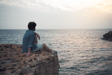 Charming dreamer. Full length back view of pensive stylish bearded male is sitting on the edge of cliff with endless ocean in background. He is looking at water thoughtfully. Copy space in right side