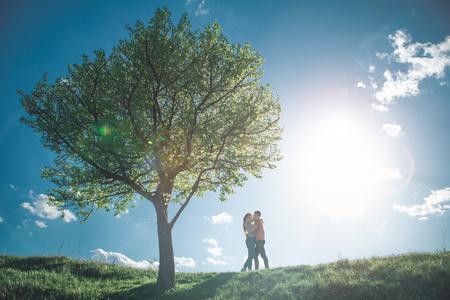 El amor está en la longitud suavemente sentimiento de amantes de la gente agradable abrazándose en la colina . besar están besando a otro otro con el verano acogedor paisaje en el fondo Foto de archivo - 103083613