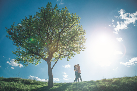 Love is in the air. Full length of nice loving people embracing on hill by tree. They are giving kisses to each other with exciting summer landscape on background