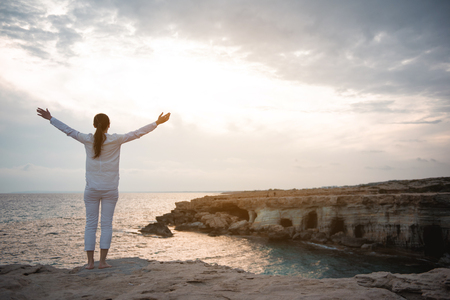 Happy life concept. Full length back view of charming girl is standing on rock with raised hands. She is looking at ocean with sunset in background. Copy space in the right side