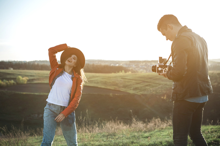 Summer photo session. Full length of joyful couple making photos on green hill. Smiling woman is posing to boyfriend holding camera with concentration