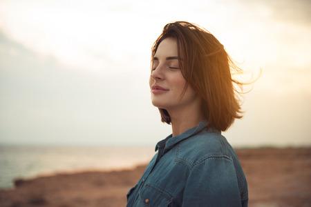 Große Freude. Charmante ruhige junge Frau steht in der Nähe des Meeres mit geschlossenen Augen und drückt Freude aus. Sie posiert gegen den wunderschönen Sonnenuntergang und genießt die letzten Sonnenstrahlen