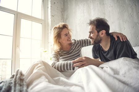 Happy two smiling people who are in love. They are meeting morning together sitting in bed and showing fondness to each other. Lady is putting arm around partner neck and looking at him with love Stock Photo
