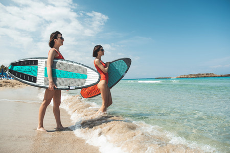 Side view profile of two female friends are carrying their surfboards while wading into the ocean to surf. They are looking at wave in anticipation. Summer vacation concept. Copy space in right side