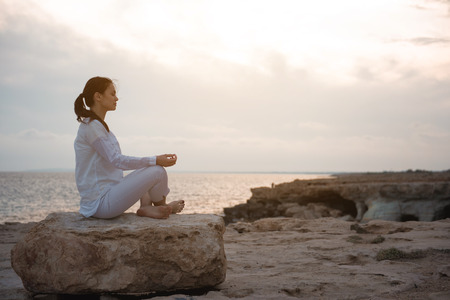 Be deep in thoughts. Full length side view of relaxed girl is sitting in lotus against beautiful ocean. She is putting elbows on knees while practicing yoga outdoors. Copy space in the right side