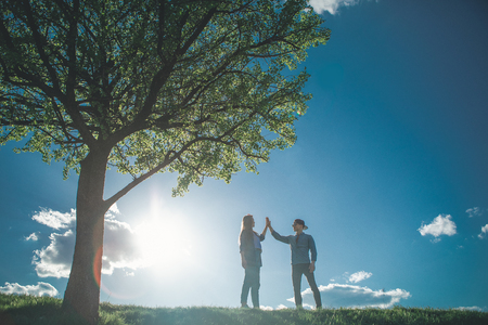 Full length of young couple walking in bright sunny day. They are standing by nice green tree opposite to each other and gently touching their hands 写真素材