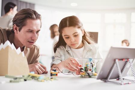 Portrait of concentrated girl and teacher looking helicopter. Hey checking it with gadget