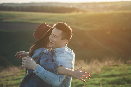 Waist up side view of laughing man hugging woman during summer sunset. Young people are full of joy and love. Copy space in right side Stock Photo
