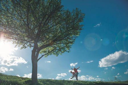 Full length of joyful man and woman having fun during their walk in sunny green meadow. They are smiled and happy. Girl sitting on back of her boyfriend raising hands up Stock Photo