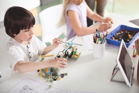 Top view concentrated kid creating helicopter from constructor while sitting at table near girl. Modern education concept Stock Photo