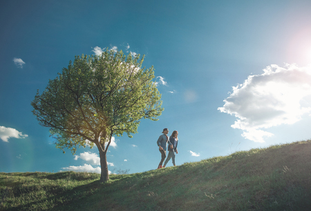 Let us go. Full length of young happy people having promenade together during warm sunny day. They are looking calm and delighted Stock Photo