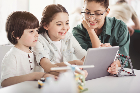 Portrait of beaming girl and glad boy with outgoing teacher looking at electronic tablet